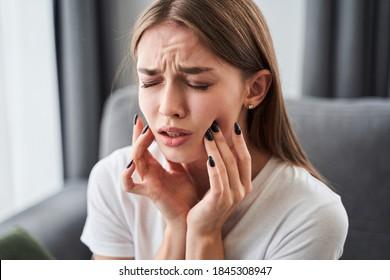 Zahnschmerzen. Mädchen, die an Zahnschmerzen leiden und die Wange berühren, während sie zu Hause auf dem Sofa sitzen. Dentalproblem-Konzept. Stockfoto