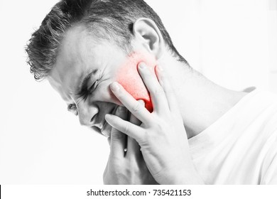 Toothache,  medicine, health care concept, Teeth Problem, young man  suffering from tooth pain, caries, In a white t-shirt on a white background, pain in the jaw