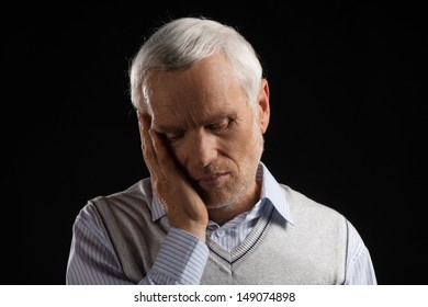 Toothache. Portrait of white hair senior man holding his hand on cheek while isolated on black