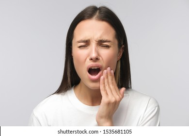 Toothache. Studio shot of young woman feeling pain, holding her cheek with hand, suffering from bad tooth ache, isolated on gray