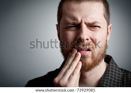 Toothache - suffering young man with teeth problems