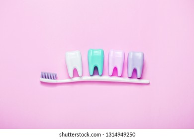 Toothbrush and big tooth on pink background. Teeth care minimalism concept. Copyspace for your text.