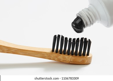 Toothbrush with black charcoal toothpaste. Close up of black toothpaste squeezing on toothbrush.