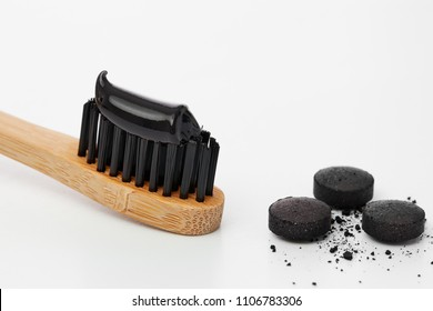 Toothbrush with black charcoal toothpaste. Black toothpaste on toothbrush with activated charcoal pills.