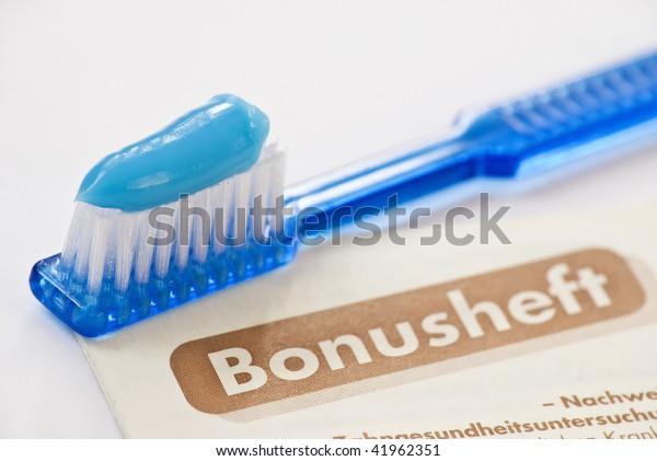 Zahnbürste mit blauer Zahnpasta und deutscher Bonusheft