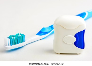 toothbrush and dental floss on white background