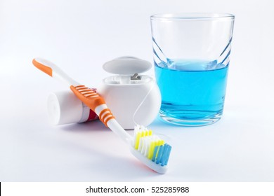 Toothbrush, dental floss, toothpaste and mouthwash on white background