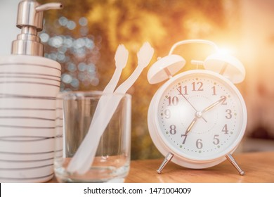 Toothbrush in glass with clock. Concept of cleaning and care of the teeth in a bathroom. oral hygiene. concept of dental care. banner size, vintage effect.