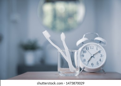 Toothbrush in glass with clock. Concept of cleaning and care of the teeth in a bathroom. oral hygiene. concept of dental care. banner size, vintage effect