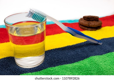 toothbrush, glass of water and chocolate cookies with colorful and white background