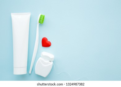 Toothbrush with green bristles, white tube of toothpaste, container of dental floss and red heart on pastel blue background. Love healthy teeth concept. Empty place for text, quote, sayings or logo.