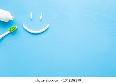 Toothbrush with green bristles, white tube of toothpaste on pastel blue background. Smiley face created from paste. Happy for healthy teeth concept. Empty place for text, quote, sayings or logo.