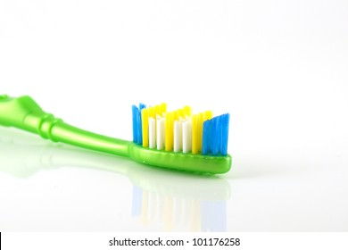 Tooth-brush with green handle over white. Shallow DOF