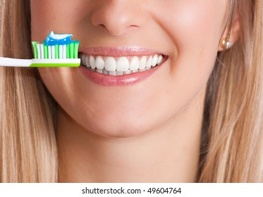 Toothbrush and healthy teeth of a white woman