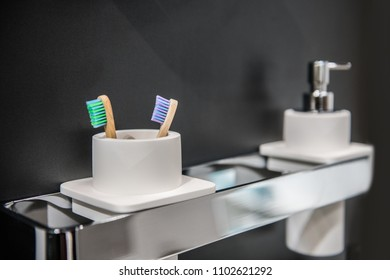 Toothbrush holder and liquid soap on holder on bathroom wall