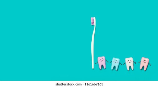 Toothbrush and many teeth on blue background. Teeth care minimalism concept. Toothbrush leads the teeth' smiling faces and funny picture