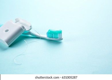 Toothbrush with paste and dental floss on color background
