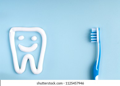 Toothbrush and tooth paste on blue. Blue toothbrush. Toothpaste art.