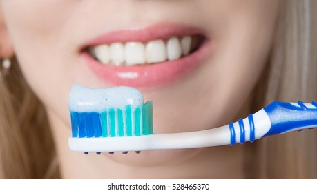 toothbrush with toothpaste at the mouth of the girl