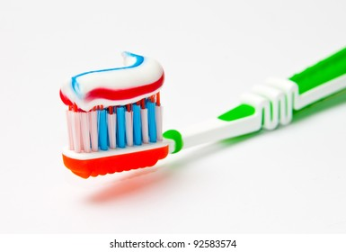 toothbrush with tricolor toothpaste  on light background