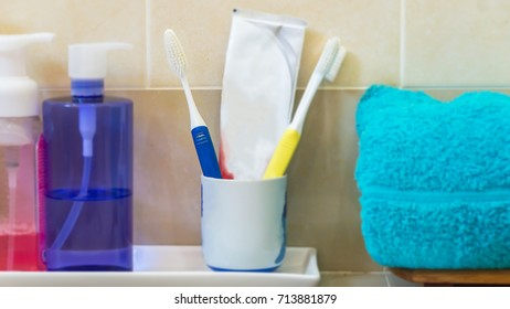 Toothbrushes with Bathroom set, dispenser and soap on stool in a bathroom closeup.