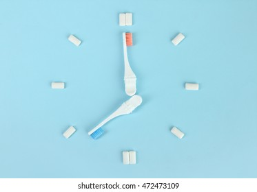 Toothbrushes, chewing gum in the form of hours on a blue background. The concept of time to brush your teeth.