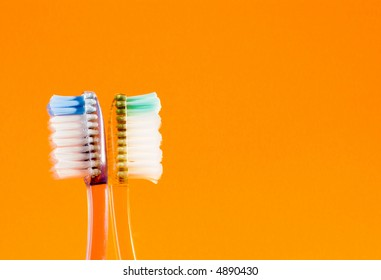 Toothbrushes facing opposite directions.