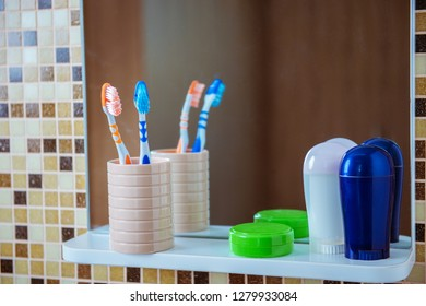 toothbrushes in the glass and deodorants for the body in the bathroom