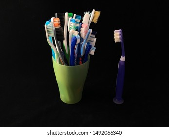 A lot of toothbrushes in a glass. Old toothbrushes in a cup on a black background. One toothbrush stands out from the others. Concept: all against one.