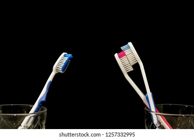 Toothbrushes have a crush on each other and make out. A jealous sad toothbrush watching. Black background for copy space.