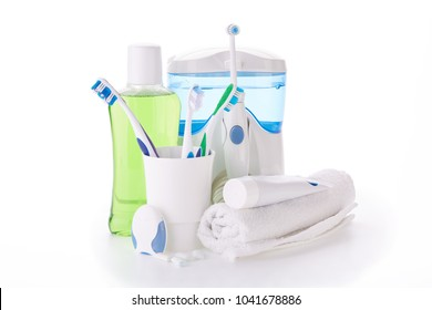 Toothbrushes, toothpaste, oral irrigator, floss, rinse, gums and fresh leaves of mint on a white background. Accessories for cleaning of teeth. Oral hygiene. Daily dental care.