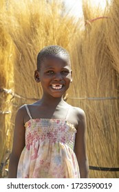 Toothless African girl, in a  village in Botswana , thatch background