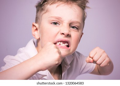 Toothless angry little boy is boxing in studio. Light background