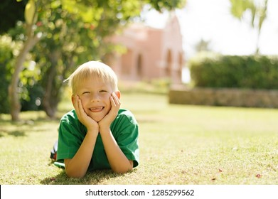 Toothless blond boy in a green sweatshirt lies on the grass in the rays of the sun with his head propped on his hands and showing his tongue against the background of the building and vegetation