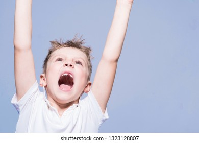 Toothless little boy with open mouth raised his hands up. Light background