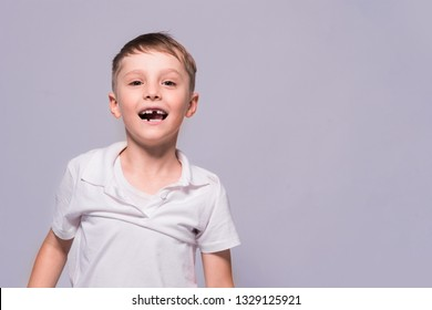 Toothless little boy in a white t-shirt is smiling. Posing in the studio.
