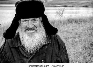 A toothless old man with a beard in a winter hat. Black and white photography