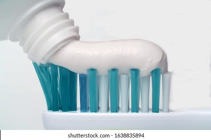 Toothpaste extruded onto a toothbrush. Dental health care or oral hygiene - Squeezing White Toothpaste From A Tube Onto A Toothbrush.