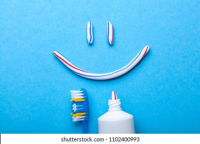 Tooth-paste in the form of face with a smile. Tube of toothpaste and toothbrush on blue background. Refreshing and whitening toothpaste.