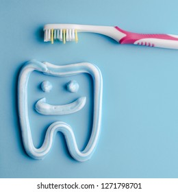 Toothpaste in a form of a smiling tooth with a pink toothbrushe on blue. Toothpaste on blue. Dental hygiene.