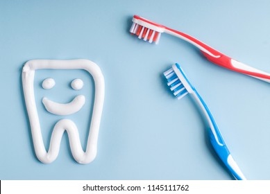 Toothpaste in a form of a smiling tooth. Red and blue toothbrushes. Toothpaste on blue. Dental hygiene.