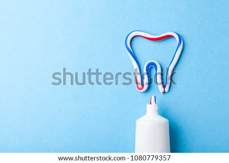 Tooth-paste in the form of tooth. Tube of the paste on blue background. Refreshing and whitening toothpaste. Copy space for text