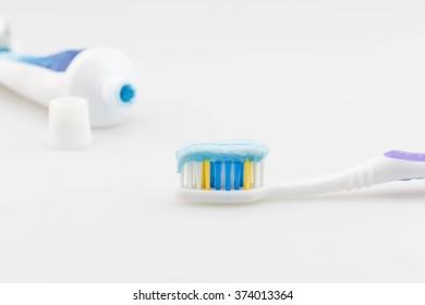 Toothpaste on a brush on white.