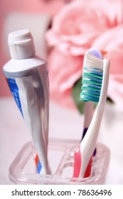 Toothpaste tube and toothbrush in pink decorated bathroom