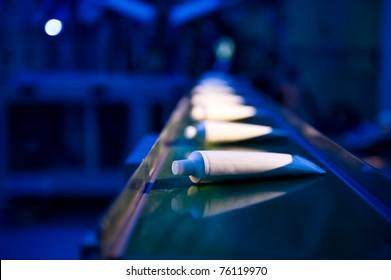 Toothpaste tubes on conveyor belt