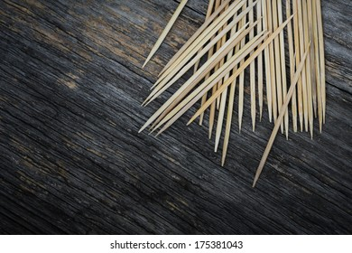 A lot of toothpicks on a textured wood background