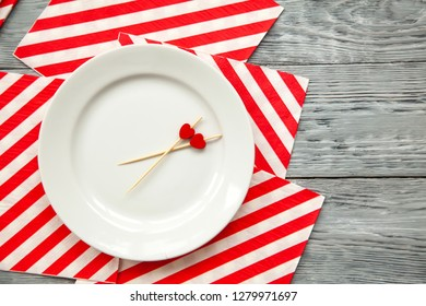 toothpicks with a small red hearts on a white plate and striped festive napkin. Top view