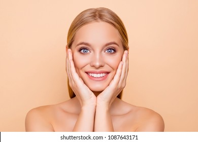 Toothy, cheerful, pretty, cute,  charming, joyful girl with perfect skin holding two palms on cheek, mask, cream, lotion, peeling effect isolated on beige background hydration moisturizing concept