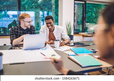 Toothy coworkers discussing funny video from social platform enjoying break for positive networking on modern laptop device,happy diverse friends laughing and using 4g wireless for browsing on netbook
