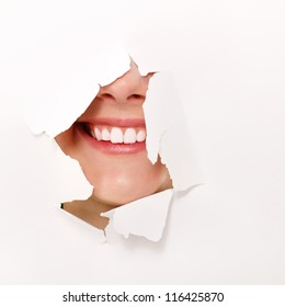 toothy smile of cheerful teen girl through hole of white paper